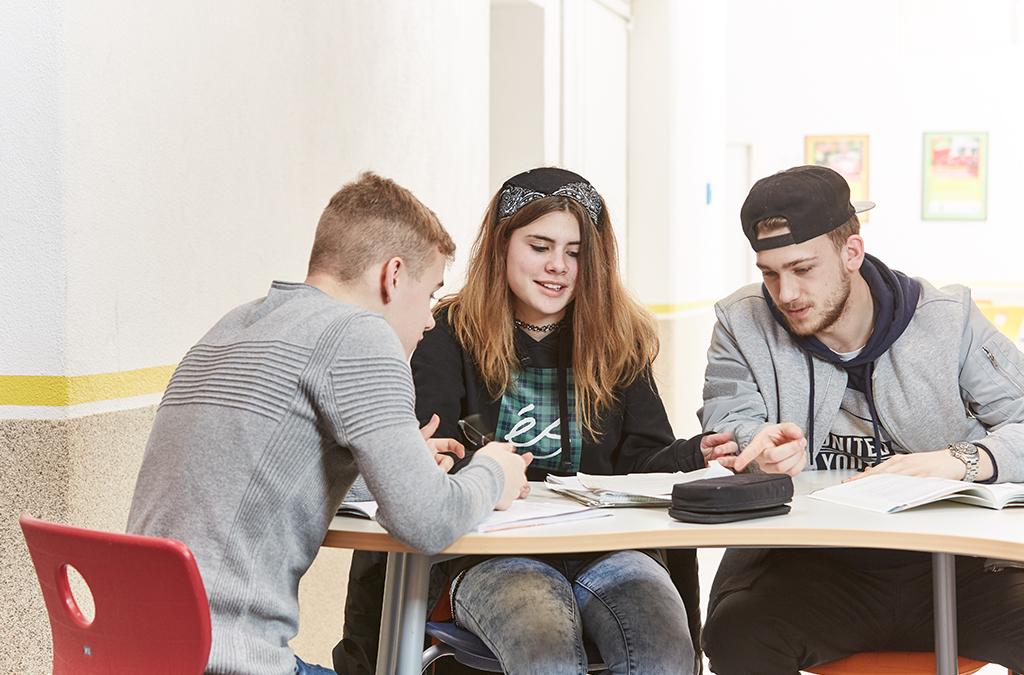 Schüler und eine Schülerin an der Carlo Schmid Schule Freiburg besprechen ein Projekt